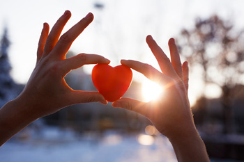 Hands holding a heart in sunlight